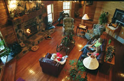 Overhead view of large room with fireplace and wooden floors, leather furniture, lamps.