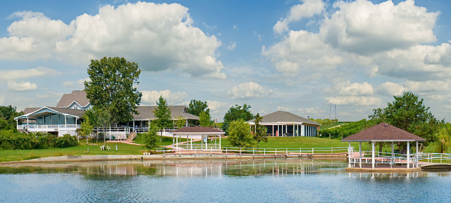 Multiple buildings along river with gazebo and dock, white railing around water, trees surrounding buildings, fluffy white clouds.