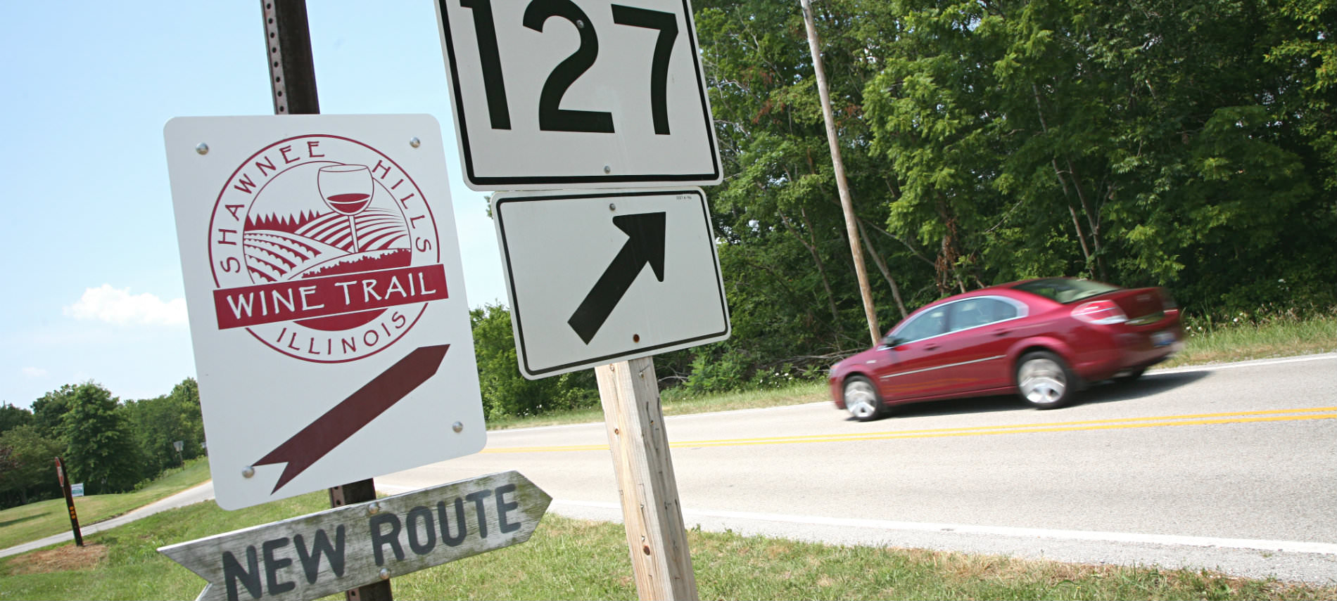 Red car on 2 lane road, road sign route 127 and Shawnee Hills Wine Trail (New Route) red and white sign.