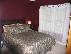 Dark burgundy bedroom with queen bed with gold and silver bedspread. Large window with white sheers. Tan Carpet.