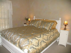 Tan bedroom with queen bed covered with gold and silver bedspread, white bed frame, white stands with lamps.