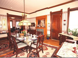 Cream dining room with rectangular glass table and wooden chairs, accent rugs on wood floor, fireplace with oak mantel.