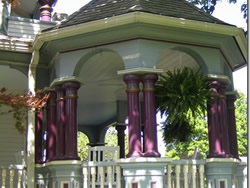 Olive covered gazebo with purple columns and white railing, hanging potted ferns.