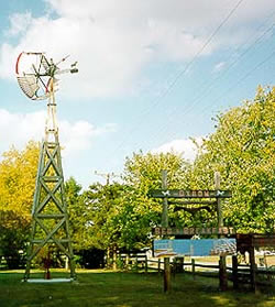 Tall metal windmill and golden trees. Wooden carved sign with text Oxbow Bed & Breakfast, telephone wires overhead.