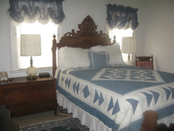 White bedroom with queen bed between two sheered windows, blue and white bedspread, stand with lamp, wooden chair.