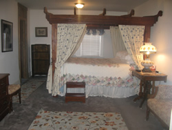 Four poster canopy bed with floral covering, step stool by bed, pictures on wall, shelf against wall, stand with lamp.