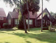 Red brick house with red roof and white trimmed windows, lawn with tall trees around property.
