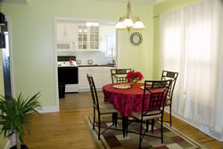 Iron table with red tablecloth and chairs by sheered window, green walls, view through doorway into kitchen.