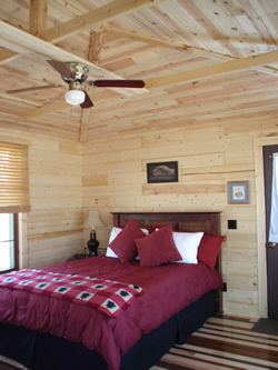 Wood walls and ceiling, queen bed with cherry headboard, burgundy comforter and blanket, window with mini blinds, ceiling fan.