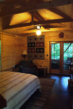Wood walls and ceiling with tan comforter on queen bed, quilt with stars on wall, ceiling fan, private balcony.