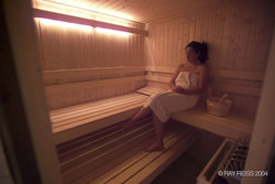Lady wrapped in white towel sitting in soothing sauna.