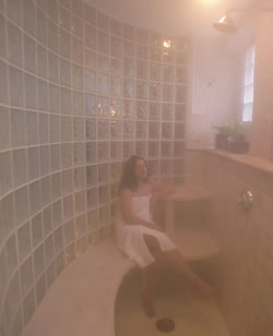 Woman in white towel leaning against glass sitting on bench in shower.