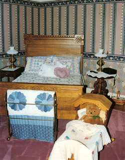 Salmon and green striped wallpaper , oak frame on queen bed with pastel comforter, baby crib with stuffed bear rose colored carpet.