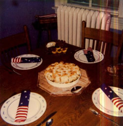 Wood table with plates and red, white and blue napkins, Pie on plate in center, heater by table.