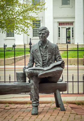 Statue of President Lincoln holding book sitting on bench by iron fence, White building with pillars in background.