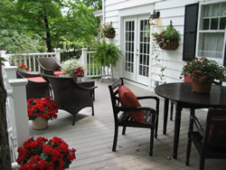 Wooden attached deck to white house with potted and hanging plants, table and chairs by window, cushioned chairs by railing.