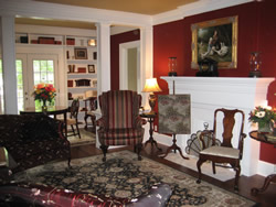 Large burgundy and yellow room room with rug, shelf with knickknacks by double entry door with windows.