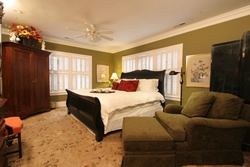 Cherry queen bed with white spread, olive walls, white ceiling fan, olive chair with ottoman, pictures on walls.