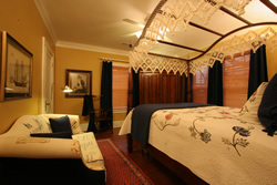 Four poster cherry bed with canopy, cream couch with blue pillows. red rugs, pictures on walls.
