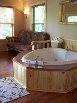 Heart-shaped jacuzzi tub with wood base, couch by windows and sconce on wall, wood floor and bathmat.