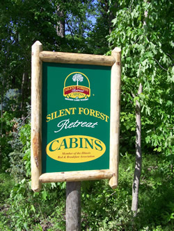 Green and yellow sign with wood border and text Silent Forest Retreat Cabins on edge of woods.