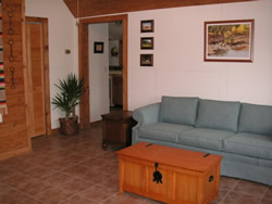 Peach walls with pictures, blue couch on linoleum floor, wooden chest, louvered closet door.