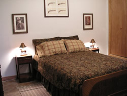 White wall with framed pictures, full bed with brown comforter and checkered shams, tan carpet, stands with lamps.
