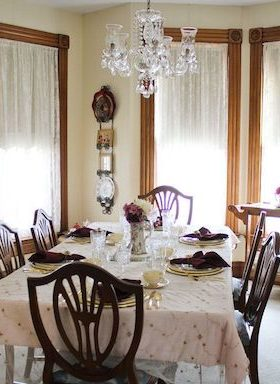 Brightly lit dining room with cream striped wallpaper, wood framed windows with sheers, crystal chandelier, china cabinet, tan carpet.