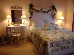 Full bed with white frame and floral comforter, dresser with mirror and lamps, ivy accents, tan carpet.