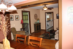 Peach painted room with dining table, ceiling fan with light fixture, open doors with views of bedroom and bathroom.