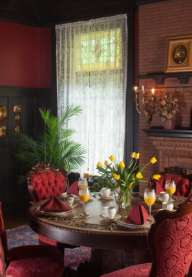 Dining room with Oak table set for meal with red cushioned chairs, Tulips in vase, Fireplace and wood hutch.
