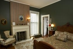 Striped wallpaper over fireplace with dark green walls, tan chair, queen cherry bed with floral comforter, window with sheers.