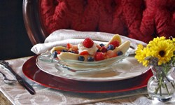 Red cushioned wood chair by table, bowl with fresh fruit of bananas, blueberries and strawberries, flowers in vase.
