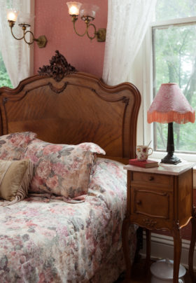 Rose wallpapered room, oak headboard on queen bed with floral comforter and shams, white robe hanging, stand with lamp.